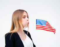 Businesswoman blowing on US flag Royalty Free Stock Image
