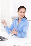 Businesswoman in a blue blouse is making her nails at desk and g Stock Photos