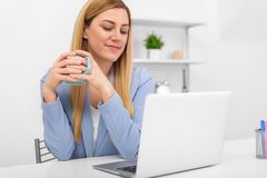 Businesswoman in a blue suit is sitting at the laptop screen in the workplace with a cup of tea or coffee in her hands. Lunch break or free working hours Stock Photo