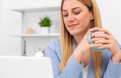Businesswoman in a blue suit is sitting at the laptop screen in the workplace with a cup of tea or coffee in her hands. Lunch break or free working hours royalty free stock image