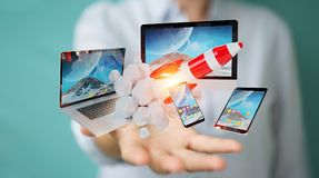 Businesswoman connecting tech devices and startup rocket 3D rend. Businesswoman on blurred background connecting tech devices and startup rocket 3D rendering Royalty Free Stock Images