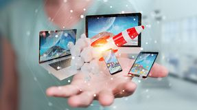 Businesswoman connecting tech devices and startup rocket 3D rend. Businesswoman on blurred background connecting tech devices and startup rocket 3D rendering Royalty Free Stock Photography