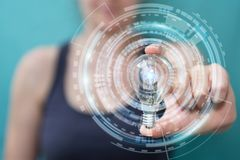 Businesswoman holding a lighbulb with connections in her hand Stock Photo