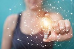 Businesswoman holding a lighbulb with connections in her hand Stock Images