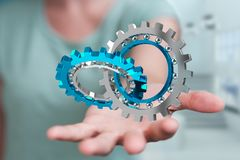 Businesswoman using floating modern gear mechanism 3D rendering. Businesswoman on blurred background using floating gear icons 3D rendering Royalty Free Stock Images
