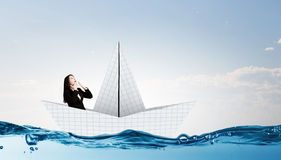 Businesswoman in boat made of paper. Successful businesswoman sailing on paper boat in financial sea Stock Image