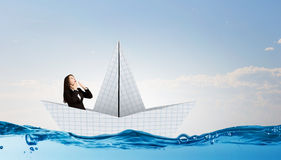 Businesswoman in boat made of paper. Successful businesswoman sailing on paper boat in financial sea Stock Photos