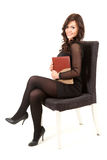 Businesswoman with book sitting on chair Stock Images
