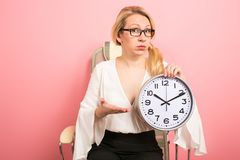 Businesswoman boss with clocks. Portrait of upset blonde businesswoman boss in eyeglasses sitting in chair isolated on pink background holding clocks and Royalty Free Stock Image