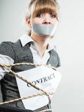 Businesswoman bound by contract with taped mouth. Stock Photography