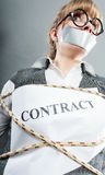 Businesswoman bound by contract with taped mouth. Stock Image