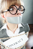 Businesswoman bound by contract with taped mouth. Royalty Free Stock Photos