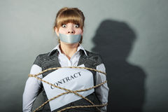 Businesswoman bound by contract with taped mouth. Stock Photo