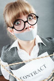 Businesswoman bound by contract with taped mouth. Royalty Free Stock Image