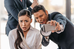 Businesswoman bound with rope while businessman taking selfie and screaming in megaphone. Asian businesswoman bound with rope while businessman taking selfie and Royalty Free Stock Photos