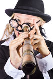 Businesswoman looking through telescope. Businesswoman in bowler hat and dark suit with thick rimmed glasses, fake mustache looking through antique telescope Stock Image