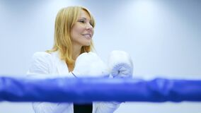 Beautiful businesswoman in boxing gloves on boxing ring stock footage