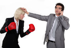 Businesswoman boxing a man Stock Photos