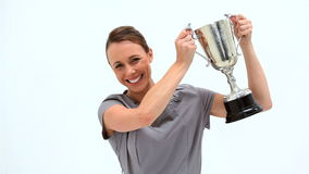 Businesswoman brandishing a trophy. Against white background stock footage