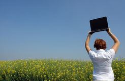 Businesswoman break. Businesswoman in the middle of a flower field with her laptop taking a break and leaving the computer aside Stock Image