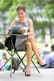 Businesswoman on break in park. Young professional business woman using tablet computer in Bryant Park, New York City, USA. Mixed race Asian Chinese / stock images
