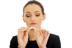 Businesswoman breaking cigarette. Royalty Free Stock Images