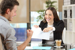 Businesswoman breaking contract with a client. Businesswoman breaking contract with a happy client at office Royalty Free Stock Photo