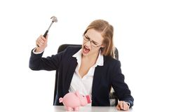Businesswoman breaking a piggybank Royalty Free Stock Photography