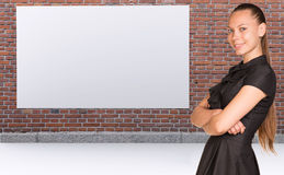 Businesswoman and brickwall with empty billboard Royalty Free Stock Images