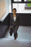 Businesswoman with briefcase climbing stairs. At office Stock Photo