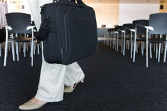 Businesswoman with briefcase leaving empty lecture hall Stock Photography