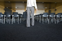 Businesswoman with briefcase leaving empty lecture hall Royalty Free Stock Image