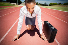 Businesswoman with briefcase in ready to run position. On running track Royalty Free Stock Photos