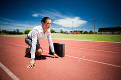 Businesswoman with briefcase in ready to run position Stock Photos