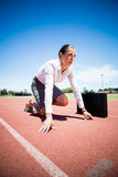 Businesswoman with briefcase in ready to run position. On running track Royalty Free Stock Images