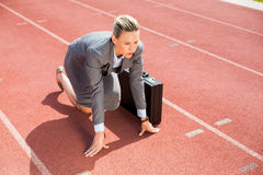 Businesswoman with briefcase in ready to run position Stock Photography