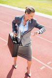Businesswoman with briefcase in ready to run position Royalty Free Stock Image