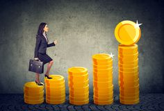 Business woman with briefcase stepping up a financial stairway ladder made of gold coins. Businesswoman with briefcase stepping up a financial stairway ladder Stock Images