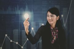 Businesswoman with bright bulb and growth graph. Picture of young businesswoman holding a bright bulb and standing with growth finance graph background royalty free stock photos