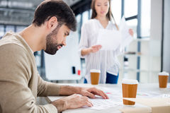 Businesswoman bringing papers to bearded young businessman looking at contract Royalty Free Stock Photos