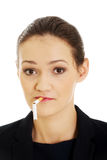 Businesswoman with broke cigarette in mouth. Royalty Free Stock Photography