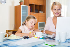 Businesswoman browsing internet at home, daughter drawing  in p Stock Photography