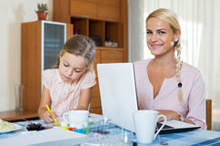 Businesswoman browsing internet at home, daughter drawing  in p Stock Image