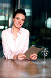 Businesswoman browsing on tablet pc with a drink beside Royalty Free Stock Photos