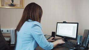 Businesswoman brunette sitting in the office and typing on the computer keyboard. Serious businesswoman with brown hair in a blue jacket is sitting at the desk stock video