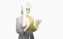 Businesswoman in building helmet with clipboard. Business, people, building, construction and architecture concept - smiling businesswoman in helmet with Stock Photo
