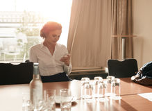 Businesswoman in business conference room using mobile phone Royalty Free Stock Images