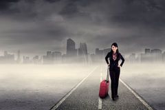 Businesswoman in the business trip. Business trip concept with a businesswoman standing on the road Royalty Free Stock Images