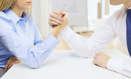 Businesswoman and businessman arm wrestling Stock Photo