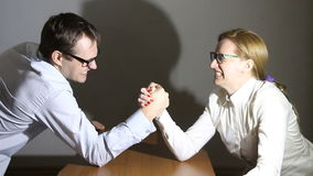Businesswoman and businessman arm wrestling at the office, Man and woman stock video footage